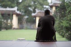 Buddhistischer Mönch sitzt auf den Schritten der Pagode lizenzfreies stockbild
