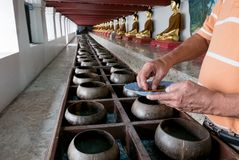 Buddhists are donating money to temple by their faith and to maintain the temple in Thailand. Give coin in alms bowl, a man put a Baht coin in a monk bowl for Stock Photo