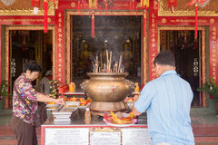Buddhists lighting up candles and joss sticks in Chinese temple. Chantaburi, Thailand - April 18, 2015: Unidentified Buddhists light up candles and joss sticks Royalty Free Stock Images