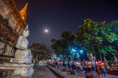 Buddhists people walking with lighted candles in hand around a ancient temple stock images