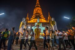 Buddhists people walking with lighted candles in hand around a ancient temple stock photo