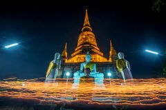 Buddhists people walking with lighted candles in hand around a ancient temple royalty free stock images