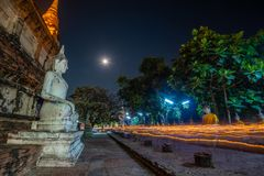 Buddhists people walking with lighted candles in hand around a ancient temple stock photography