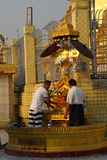 Buddhists pray at the planetary post. YANGON, MYANMAR - MAR 2, 2015 - Buddhists pray at the planetary post of their birth day,  Botataung Pagoda, Yangon Royalty Free Stock Photo