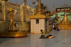 Buddhists pray at the planetary post. YANGON, MYANMAR - MAR 2, 2015 - Buddhists pray at the planetary post of their birth day,  Botataung Pagoda, Yangon Royalty Free Stock Photography