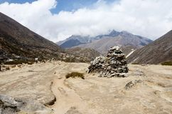 Buddhists prayer flags and stone pyramids in Himalaya mountains Royalty Free Stock Image