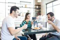Buddies Having Refreshment In Coffee Shop. Male and female friends enjoying coffee and chouxs at table in cafe royalty free stock photos