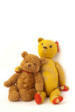 Buddies New and Old. An old and new teddy bear sitting side-by-side, one with its arm over the others shoulder Stock Photography