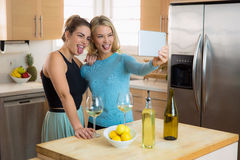 Buddies taking selfie on a tablet making goofy funny faces laughing and being young and silly Royalty Free Stock Photos