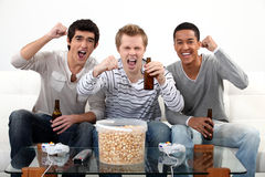 Buddies watching football. Match on telly Stock Photos