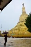 Buddist eller munk som går på den Shwemawdaw Paya pagoden i Bago, Myanmar Arkivfoton
