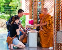 Buddist monk blesses religious people at Damnoen Saduak temple, Thailand Royalty Free Stock Photo