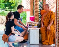 Buddist monk blesses religious people at Damnoen Saduak temple, Thailand Royalty Free Stock Photos