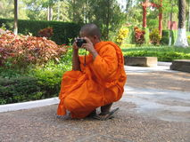 Buddist monk with a camera Stock Photo