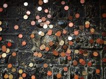 Buddisten är stället per mynt i fotspår av buddha Arkivbild