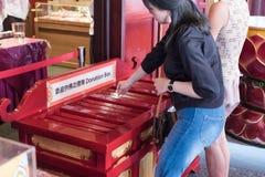 Buddisten gör en merit in i donationasken på templet och museet för Buddhatandrelik Royaltyfri Bild