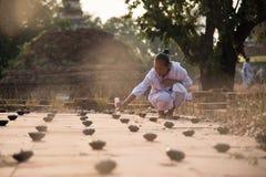 Buddisten häller olja in i lampa 03 fotografering för bildbyråer