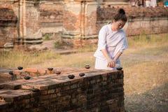 Buddisten häller olja in i lampa 01 Arkivbild