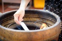 Buddisten har bränningpapper i behållaren, därför att det är tro Arkivbild