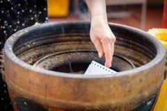 Buddisten har bränningpapper i behållaren, därför att det är tro Arkivbilder