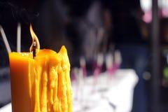 Buddister gör merit och att förlägga en tänd stearinljus och tände rökelse med stearinljusramen på templet Selektivt fokusera arkivbilder
