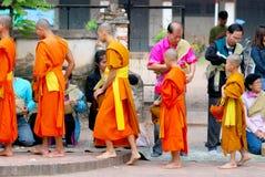 Buddister ger mat till munkar för merittid Royaltyfri Bild