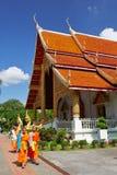 Buddister som går vid korridoren i Wat Phra Singh i Chiang Mai Arkivfoton