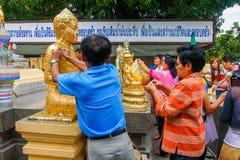Buddisti che dorano la foglia di oro sul fronte dello staue di Buddha Fotografia Stock