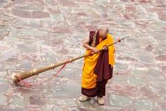 Buddistisk munk med Dungchen Fotografering för Bildbyråer