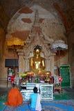 Buddistisk munk och myanmar kvinna som ber till Lord Buddha guld- st Fotografering för Bildbyråer