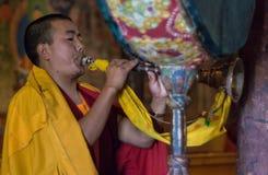 Buddistisk munk som spelar det traditionella instrumentet Arkivbild