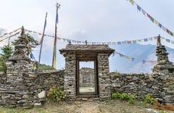 Buddistisk sten som göras port med bönflaggor Arkivbilder
