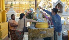 Buddistiska fantaster som badar Buddhastatyer på den Shwedagon pagoden royaltyfria foton