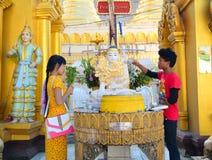 Buddistiska fantaster som badar Buddhastatyer på den Shwedagon pagoden arkivfoto