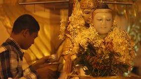 Buddistiska fantaster som badar Buddhastatyn för välsignelser på Shwedagon arkivfilmer