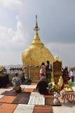 Buddistiska fantaster som ber av det guld-, vaggar framme på den Kyaiktiyo pagoden Fotografering för Bildbyråer