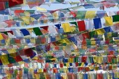 Buddistiska ljusa prayerful flaggor med religiös text i sanskritiskt mot bakgrund för blå himmel Royaltyfri Fotografi
