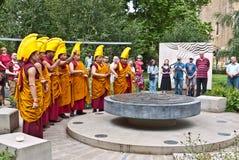 Buddistiska monks rymmer en ritual i fredträdgårdarna Arkivfoton