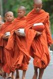 Buddistiska monks som bär matskålar, Cambodja Royaltyfria Foton