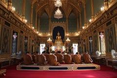 Buddistiska munkar ber i den huvudsakliga korridoren av Wat Ratchabophit, i Bangkok (Thailand) Arkivbild