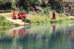 Buddistiska munkar för barn och deras reflexion i floden Buddistiska munkar för barn och deras reflexion i floden royaltyfria foton