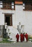 Buddistiska munkar går till ingången av en tempel nära Thimphu (Bhutan) Royaltyfri Fotografi