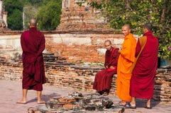 Buddistiska munkar i långa ämbetsdräkter som går i, parkerar i Thailand fotografering för bildbyråer