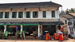 Buddistiska munkar, Luangprabang, Laos med kvinnan och behandla som ett barn i fönster Royaltyfri Bild