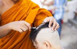 Buddistiska munkar rakar deras hår Arkivbilder