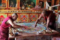 Buddistiska munkar som gör sandmandalaen Arkivbilder