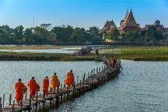 Buddistiska munkar som marscherar för att söka allmosa medan köpman som går till Arkivbilder