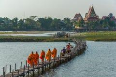 Buddistiska munkar som marscherar för att söka allmosa medan köpman som går till Royaltyfria Foton