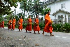 Buddistiska munkar som samlar allmosa i Luang Prabang, Laos arkivbilder