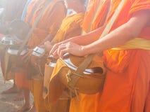 Buddistiska munkar som väntar på mat som erbjuder i morgonen Arkivbild